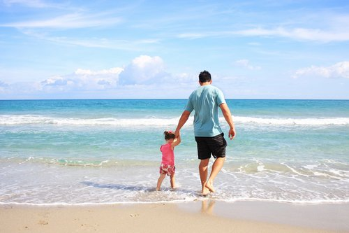 Father and child enjoying the surf in Bermuda - Budget Bermuda Travel Guide